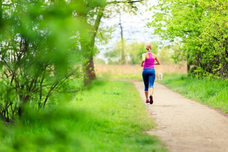 Woman runner running and walking in park, summer nature, exercising in bright forest outdoors